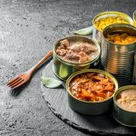 Various open tin cans of canned food on a stone Board with a fork.
